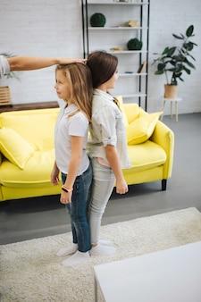 Два счастливых подростка стоят спиной к спине в комнате и улыбаются. взрослая рука на голову девушки. он измерил ее рост. брюнетка девушка выглядит выше.