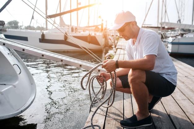 白い帽子とシャツが桟橋にチームの位置に座っている男の写真。彼はたくさんのロープを持っています。男は穏やかで平和です。彼は集中しています。