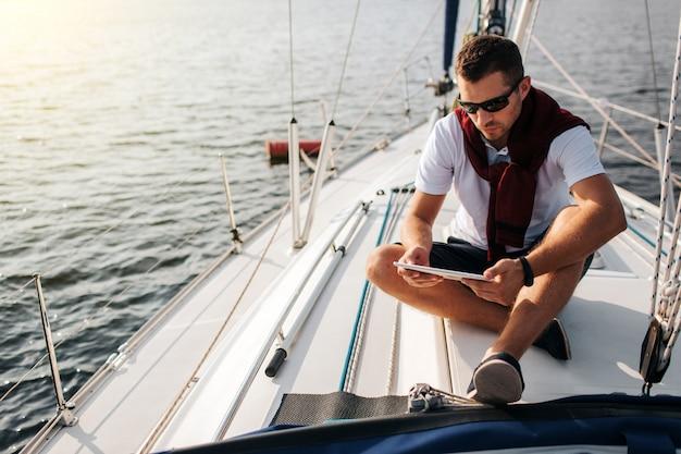 深刻で平和な男がヨットのボードに座っています。彼はタブレットを握って見ます。若い男は落ち着いています。彼はショーツと白いシャツと暗いセーターを着ています。