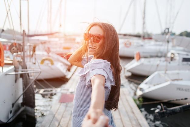 暗い髪の少女は桟橋の上に立って笑顔します。彼女の髪は手を振っています。彼女はサングラスをかけ、手を握っています。ブルネットは縞模様のドレスを着ています。彼女は幸せそうです。フォローしてください。