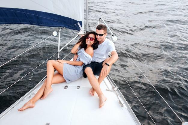 座っているとヨットの弓の上に横たわる若くて美しいカップルの写真。彼らはサングラスをかけています。 。ブルネットの笑顔。彼は足を組んで座って、楽しみにしています。