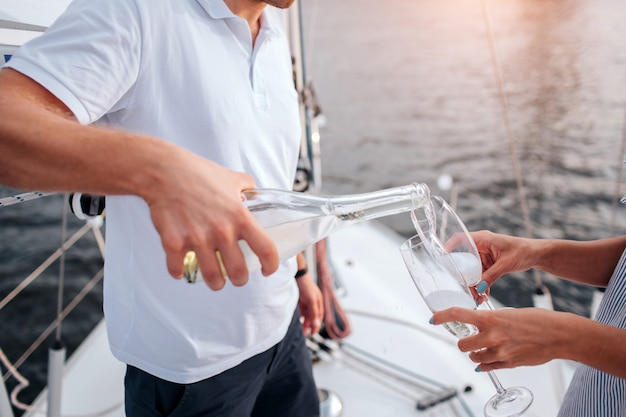 グラスにシャンペーンを注ぐ男のビューをカットします。女性はそれらを保持します。彼らは白いヨットの船首に立っています。男は白いシャツとダークショートパンツを着ています。