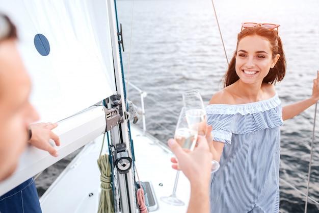 若い男性と女性が一緒に乾杯します。彼らはお互いのグラスに触れます。ブルネットは男と笑顔を見てください。彼女は管を握っている。男は深刻な視力で彼を見ます。