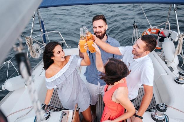 Четыре человека стоят рядом друг с другом и приветствуют бутылками пива. они смотрят вверх и улыбаются. люди счастливы.