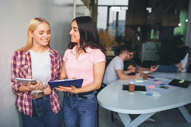 Веселые и позитивные молодые женщины улыбаются вместе. они стоят в белой комнате. модели держат трюк и пластиковый планшет. двое молодых людей сидят за ними за столом и работают.