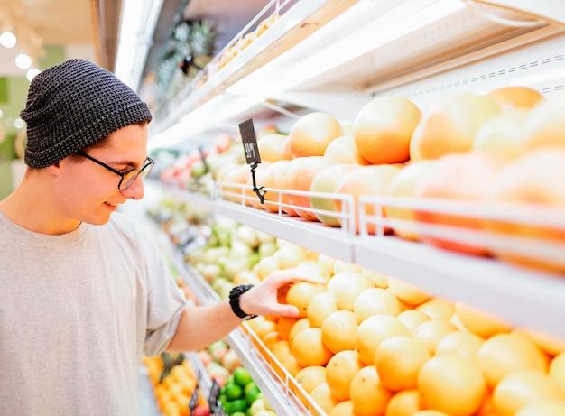 Красивый молодой человек держит апельсин
