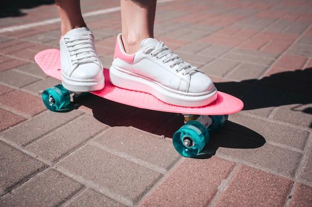 スケーターの女の子の足のクローズアップと足は白いスニーカーを着ています。女の子は両足でピンクのスケートに代わっています。外には晴れた日があります。