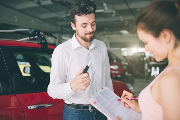 若い女性と話し、ショールーム内に新しい車を見せてフレンドリーな車のセールスマン