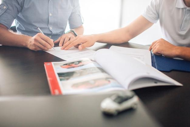 書類に署名するテーブルに座っている男性