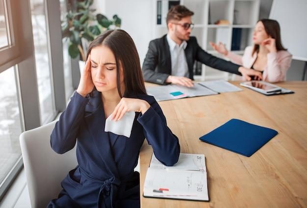 Больная молодая женщина сидеть за столом возле окна. она держится за голову и страдает. женщина держать глаза закрытыми. ее партнеры работают позади.