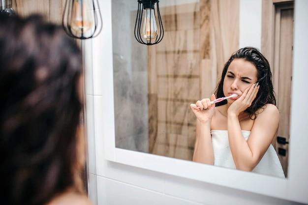 鏡で朝の夜のルーチンを行う若いスポーティな黒髪の美しい女性。彼女は歯をきれいにし、歯の痛みに苦しんでいます。モデルは鏡で見てください。白いタオルで体を包みます。