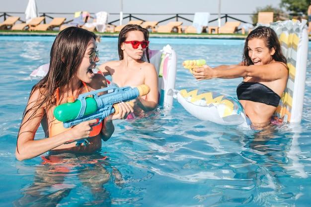 スイミングプールで遊んで楽しんでいるモデルの写真。彼らは戦います。若い女性が水鉄砲でお互いに撃ちます。セクシーなモデルは良いゲームを持っています。