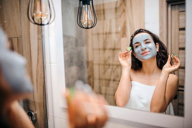 Молодая спортивная темноволосая красивая женщина делает утреннюю рутину в зеркало. она смотрит и улыбается. модель держат два кусочка огурца для глаз.