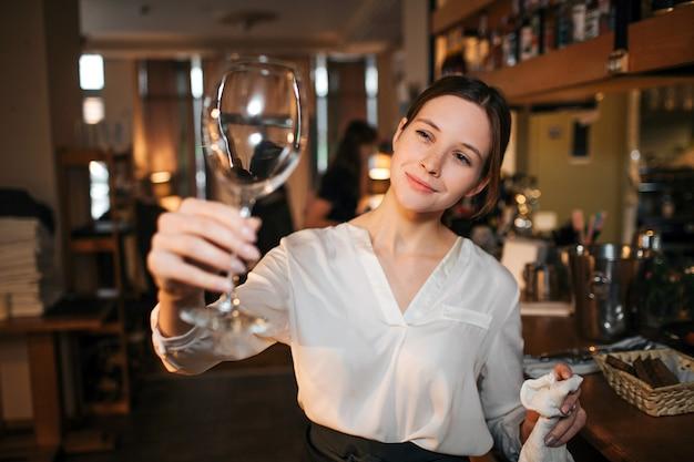 Изображение молодой официантки стоит и смотрит на чистый бокал для вина. она держит белое полотенце в другой руке. официантка работает в баре в ресторане.