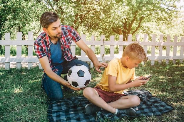 いい父親が息子を見てボールを握っています。彼は息子と遊びたいです。子供は電話で遊んでいます。彼はサッカーをしたくありません。