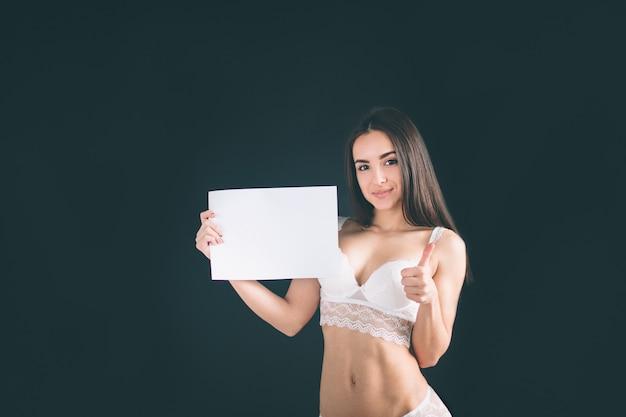 Молодая девушка держит пустой баннер. молодая женщина с длинными черными волосами стоит изолированные на черной стене. у девушки спортивная фигура, она одета в белое нижнее белье. красивые трусики и бюстгальтер.