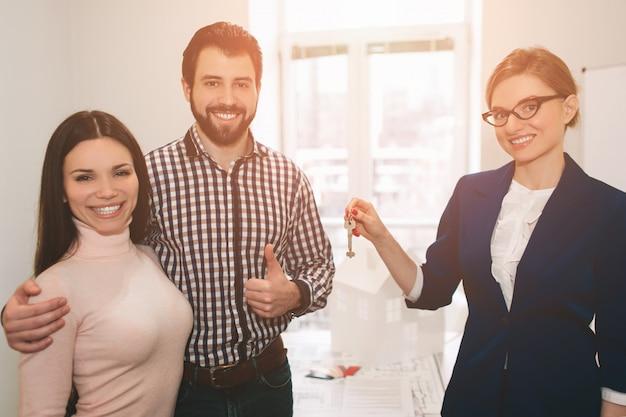 若い家族カップルが賃貸不動産を購入します。男性と女性に相談するエージェント。家やアパート、アパートを購入するための契約書に署名する。カップルのお客様にキーを提供します。