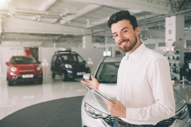 フレンドリーな車のセールスマンがショールームで新車を提示します。モーターショーで新しい車を示す若い男性コンサルタントの写真。レンタカーのコンセプト。