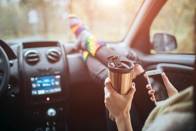 秋、オートトラベル。車での遠征中に飲むコーヒーを飲む女性のクローズアップ。車のダッシュボードに暖かい靴下で女性の足。飲んでコーヒーを飲み、スマートフォンを道路で使う
