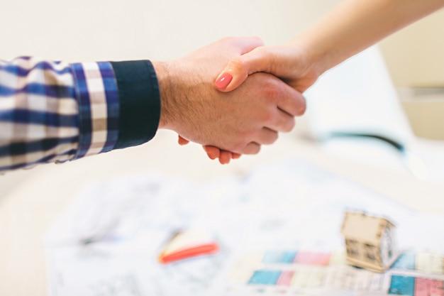 若い家族カップルが賃貸不動産を購入します。男性と女性に相談するエージェント。家やアパート、アパートを購入するための契約書に署名する。握手 。握手