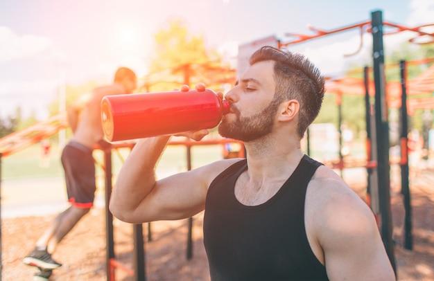 鉄の瓶と飲料水を保持している男。若いハンサムなよく形成されたスポーティな男は屋外でトレーニングした後休憩します。男性フィットネスモデルトレーニングトレーニング。