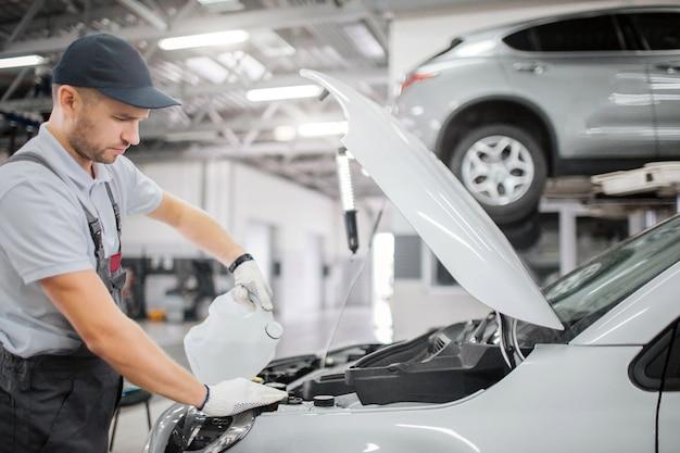 Рабочий стоит у открытой передней части кузова автомобиля. он наливает бензин из канистры. он сосредоточен. молодой человек работает в гараже.
