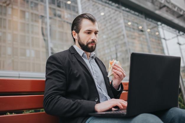忙しい人は急いでいます、彼には時間がありません、彼は外出先でおやつを食べるつもりです。労働者が食事をし、コーヒーを飲み、電話で話していると同時に。複数のタスクを行うビジネスマン。