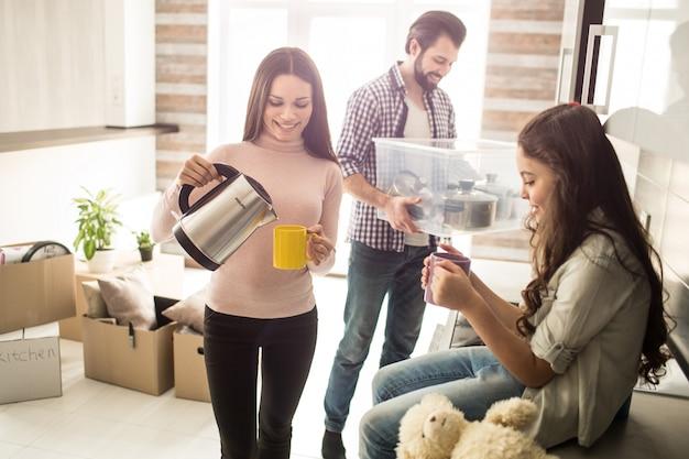 Хорошая и веселая семья стоят в светлой квартире. мужчина держит коробку с кастрюлями. женщина кладет в чашку горячую воду из электронного чайника маленькая девочка смотрит на чашку.