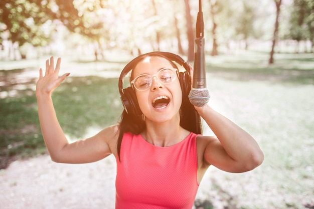 Изображение наушников эмоциональной девушки нося и слушая музыки через его. также она поет под микрофон на улице в парке. она наслаждается моментом.
