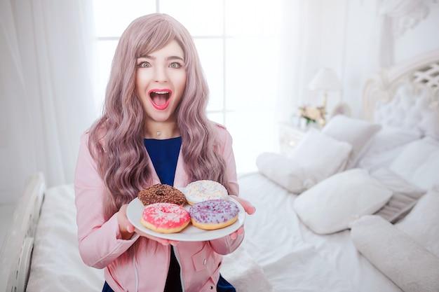 おしゃれなフリーク。長い薄紫色の髪を持つグラマー幸せな美しい女性の肖像画は、白い寝室に座っている皿の上にカラフルなドーナツを持っています。美しさとファッションのコンセプトです。