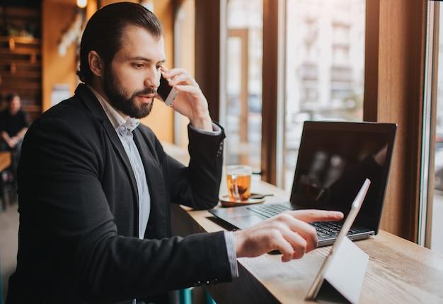 忙しい人は急いでいます、彼には時間がありません、彼は食事をして仕事をするつもりです。労働者が食事をし、コーヒーを飲み、電話で話していると同時に。複数のタスクを行うビジネスマン。