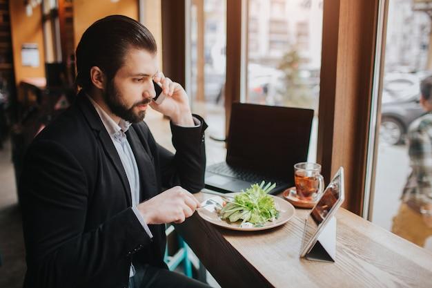 Занятый человек спешит, у него нет времени, он собирается есть и работать. работник ест, пьет кофе, разговаривает по телефону, одновременно. многозадачность делового человека.