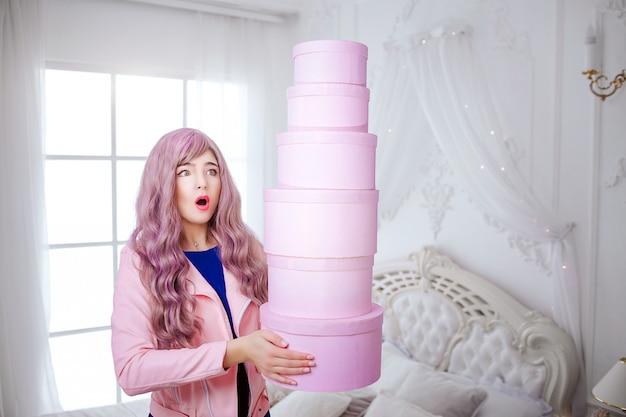 おしゃれなフリーク。長い薄紫色の髪を持つ魅力的な感情的な美しい女性は白い寝室に立っている間ピンクの箱を持っています。美しさとファッションのコンセプトです。