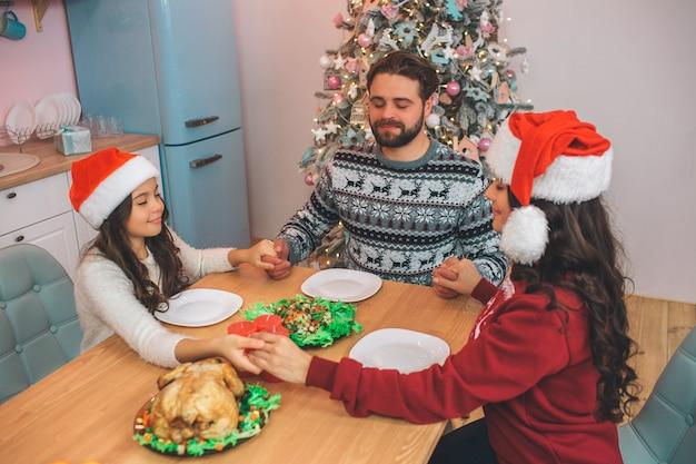 Приятные и восхитительные члены семьи сидят за столом и играют. они держат друг друга за руки и держат глаза закрытыми. они молятся перед едой праздничной еды.
