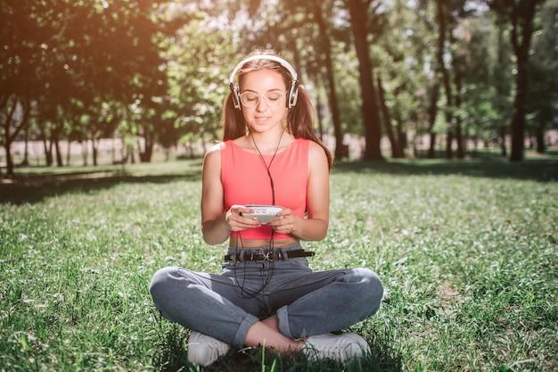Мирная и расслабленная девушка сидит на траве со скрещенными ногами и слушает музыку. у нее наушники на ушах. девушка смотрит на музыкальный плеер и улыбается.