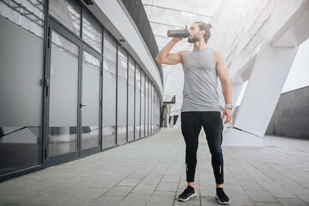 ドアに立っている運動選手と黒いボトルから水を飲むの写真。彼には休息があります。男は一人です。