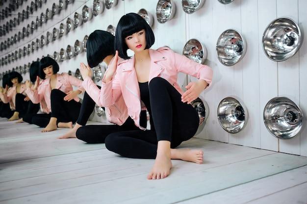 ファッションマニア。グラマーシンセティックガール、空の顔と短い黒い髪の偽の人形がスタジオに座っています。電球の近くのピンクのジャケットでスタイリッシュな美しい女性。ファッションと美容のコンセプト
