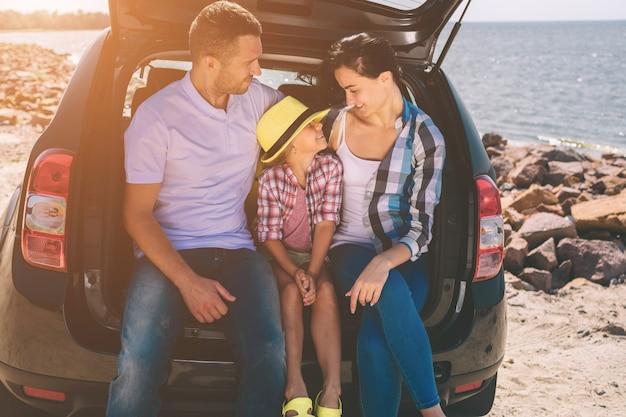 車での遠征で幸せな家族。お父さん、お母さん、娘は海や海、川を旅しています。自動車での夏のライド