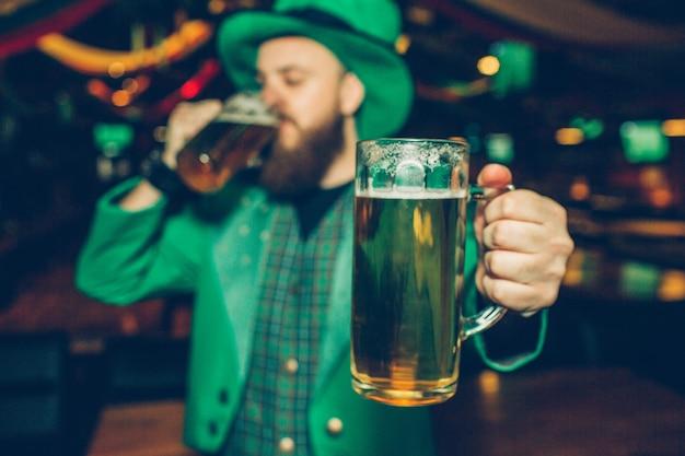 Молодой бородатый человек в зеленом костюме держать одну кружку пива рядом с камерой. он пьет из другого. парень стоит в пабе. он носит костюм святого патрика.