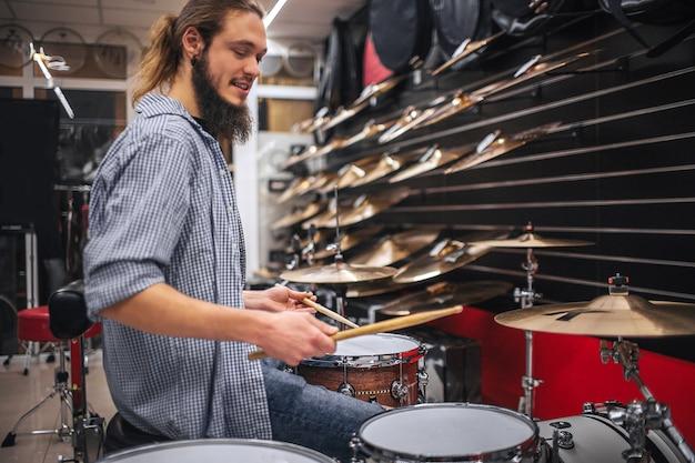Молодой бородатый парень сидит рядом с барабанами и тарелками и играет на них