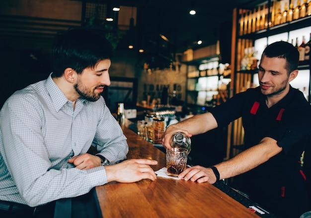 バーテンダーのスタンドに座って、バーテンダーがアルコールを注いでいる様子を見る顧客