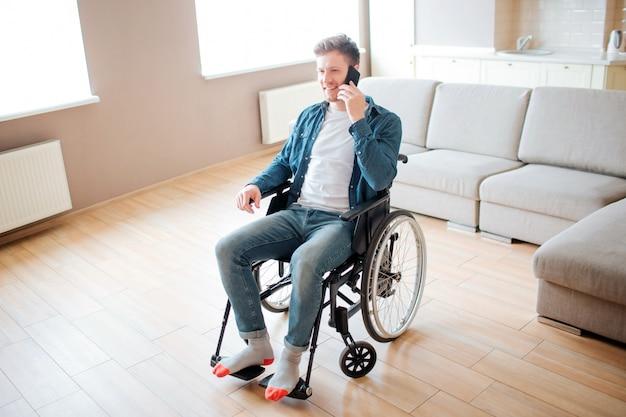 車椅子に座っていると電話で話している障害を持つ若い学生