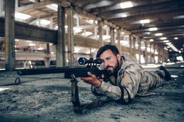 魅力的で深刻な男は、大きな格納庫で地面に横たわっています。彼は狙いを定めています。レンズを通して見る男。彼はとても落ち着いていて集中しています。