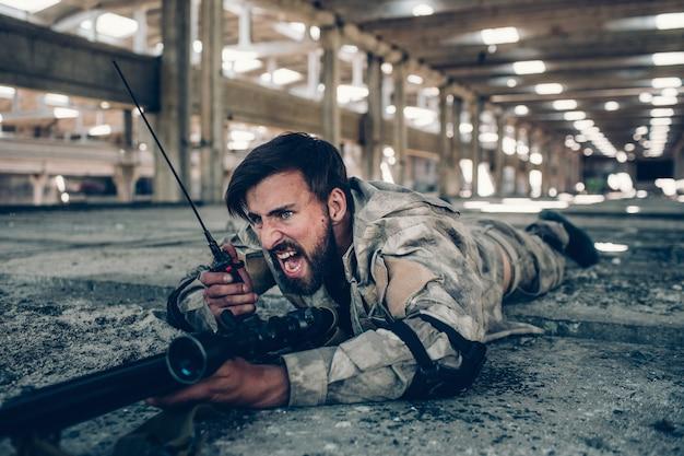 Воин кричит в портативном радио. он лежит на земле с большой винтовкой. парень имеет защиту на локтях. также он держит палец на спусковом крючке.
