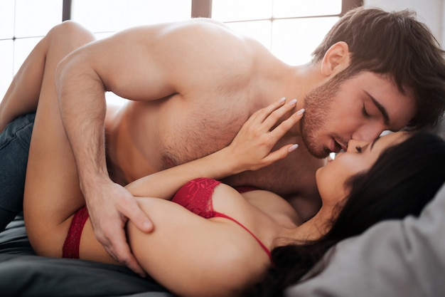 セクシーな若い裸のカップルがベッドに横になっているとキスします。彼らはお互いに触れます。赤いランジェリーの女性の上に横たわる情熱的な若い男。