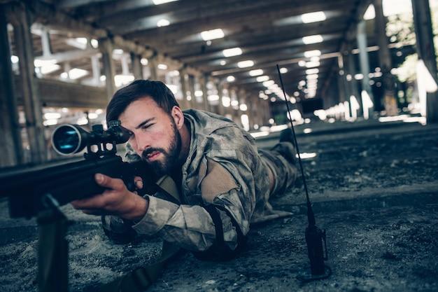 Спокойный и умиротворенный молодой человек лежит на земле и целится. он выглядит очень серьезно. парень использует винтовку для этого. также он смотрит в объектив. парень ждет.