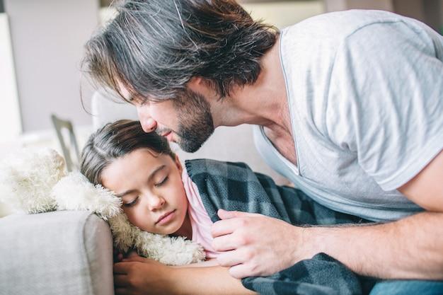 Девушка уснула. она покрыта одеялом. ее папа сидит рядом с ней. он собирается поцеловать ребенка.