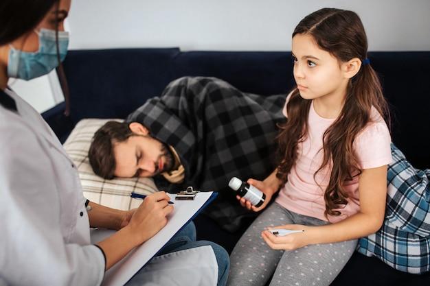 Серьезные маленькая девочка взгляд на женщина-врач. она держит бутылку сиропа в руках. больной молодой человек лежал на кровати, покрытой одеялом.
