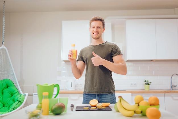 若いハンサムな男は、台所で新鮮な果物を切っている間親指とオレンジジュースを保持しています。健康食品。ベジタリアンミール。ダイエットデトックス