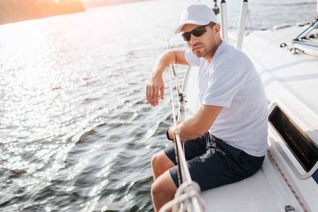 素敵で自信を持って若い男がヨットボードに座っているし、メガネ越しにカメラを見てください。彼はヨットの端にいます。男は手すりに寄りかかっています。若い男は穏やかで平和です。